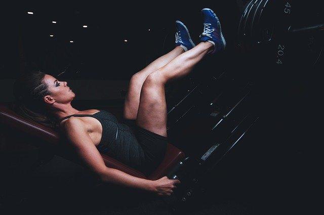 Žena v čiernom tričku cvičí na stroji a posilňuje nohy.jpg