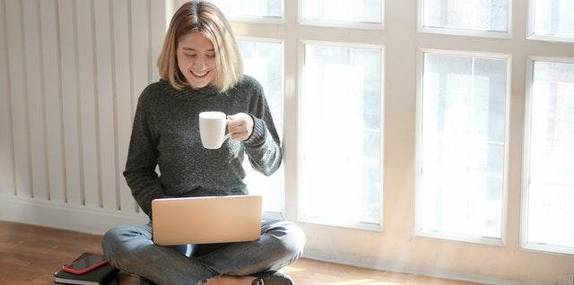 Žena so šálkou v ruke sedí pri okne a pozerá do notebooku